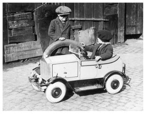 Boys playing with toy car, 1930s