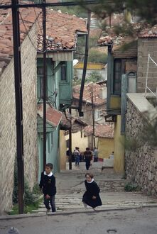 Children climb steps in a narrow street in the town of Bursa