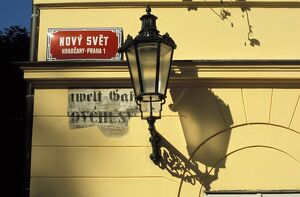 Close-up of current and historical street signs with lamp on a wall, Hradcany