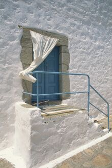 Close-up of stairs with blue rail and door of a whitewashed