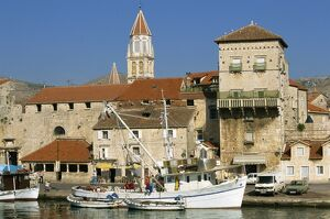 Fishing boats in harbour, with houses and tower beyond in the town of Trogir