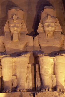 Floodlit colossi of Ramses II (Ramesses the Great), seated statues on facade of temple