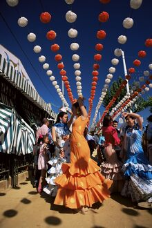 Girls dancing a sevillana beneath colourful lanterns