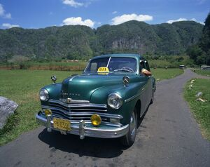 A green Plymouth taxi, a classic pre-Castro American car, in Two Sisters Valley