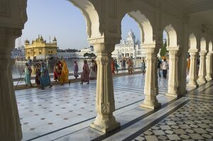 Group of Sikh women pilgrims walking around holy pool