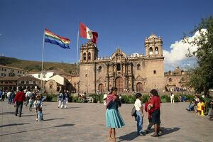 Groups of people and flags flying in front of the cathedral in Cuzco