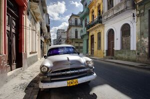 Old American Plymouth car parked on deserted street of old buildings, Havana Centro