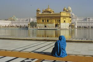 A pilgrim in blue sits by the Holy Pool of Nectar at