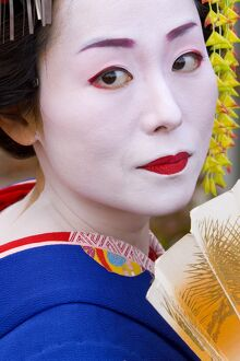 Portrait of a geisha holding a traditional paper fan