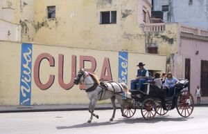 Tourists in a horse carriage passing a wall sign saying 'Live free Cuba'