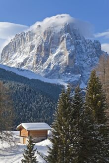 Winter snow covered mountain hut in front of Sassolungo mountain, 3181m