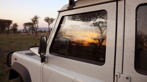 Tanzania, Serengeti. Sunrise over the bush is reflected in the window of a Land Rover