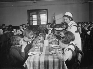 The dinner lady serving lunch at a girls school in Orpington , Kent . 1937
