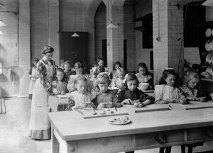 Edwardian school. Young girls, in the classroom, being supervised by their teacher