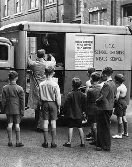 "Schoolboys watch one of their ""meals-on-wheels"" arriving. Every day in various cooking centres"