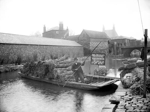 FISHER ROW, Oxford, Oxfordshire. The waterman Abel Beesley on his punt full of bundles of rushes with old Pacey Bridge in the background. Photographed by Henry Taunt in 1901