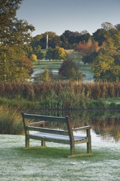 AUDLEY END HOUSE AND GARDENS, Essex. A bench in the foreground with frost settling around the pond, with Lady Portmouth's Column in the distance