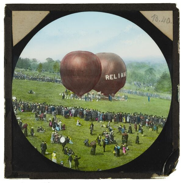 A hand-coloured lantern slide showing Shadbolt's balloon 'Reliance', and a second balloon preparing to take off from the grounds of Alexandra Palace, with large crowds watching the event