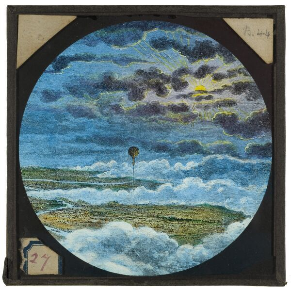 Tales of balloon flight. A hand-coloured engraving of a balloon flying above a town or city - probably London. From the Cecil Victor Shadbolt collection of lantern slides dating from 1882-1892