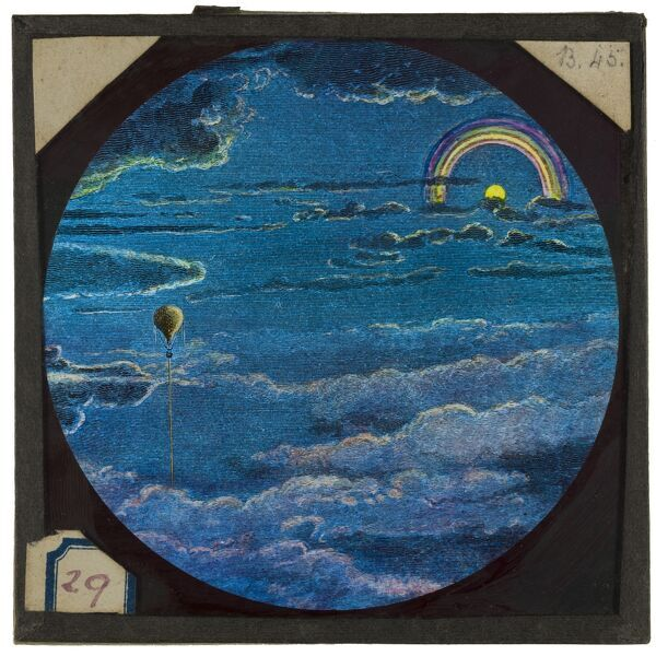 Tales of balloon flight. A hand-coloured engraving of a balloon in flight, with a rainbow in the background. From the Cecil Victor Shadbolt collection of lantern slides dating from 1882-1892