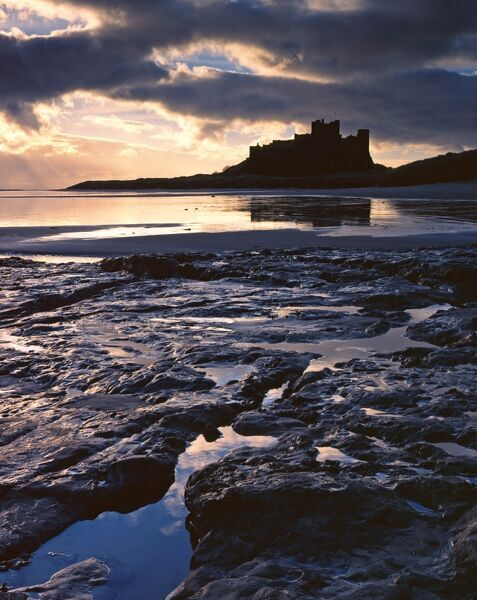 BAMBURGH CASTLE, Northumberland. The coastal castle viewed from the beach, silhouetted against a setting sun