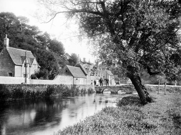 BIBURY, Gloucestershire. Looking along the river towards the stone bridge beside Arlington Row. The Cotswold village of Bibury was described as the most beautiful village in England by William Morris. Photographed in 1906 by Henry Taunt