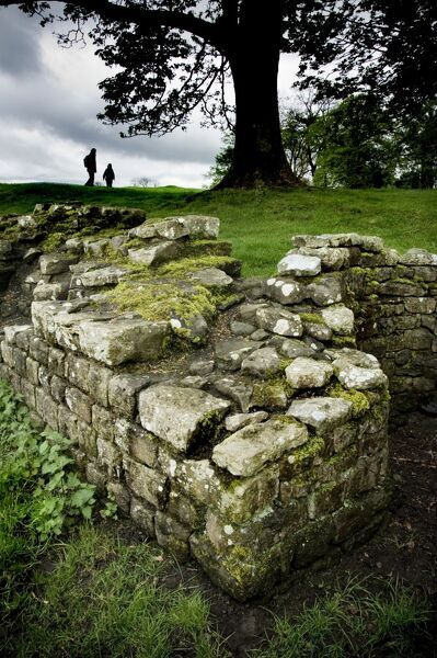 HADRIAN'S WALL: BIRDOSWALD ROMAN FORT, Cumbria. Remains of Roman walls with tree and visitors on the horizon. hadrian