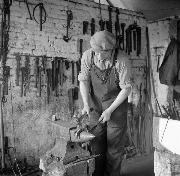 Woodbastwick, Norfolk. Interior of blacksmiths shop. A farrier shapes a horseshoe on his anvil. Photographed by Hallam Ashley, February 1949