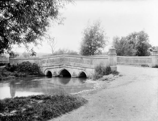 BOURTON BRIDGE, Bourton-on-the-Water, Gloucestershire. A picturesque Cotswold scene showing the bridge over the river Windrush at a crossing point which has been in use since Roman times. Photographed by Henry Taunt in 1893
