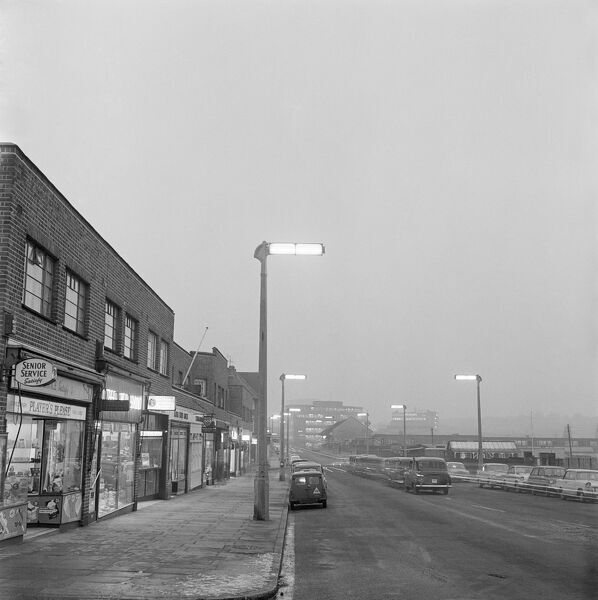 BRIDGE ROAD, Wembley, London. Looking along the shop fronts of the parade of shops at Nos 7 to 31 Bridge Road on a misty morning or evening in winter, looking towards Wembley Park Station with cars and taxis parked