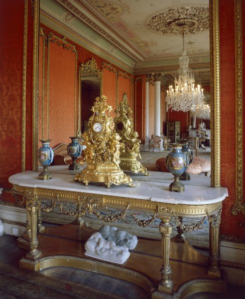 BRODSWORTH HALL, South Yorkshire. Interior view. Table with ornate clock in front of mirror in the Drawing Room