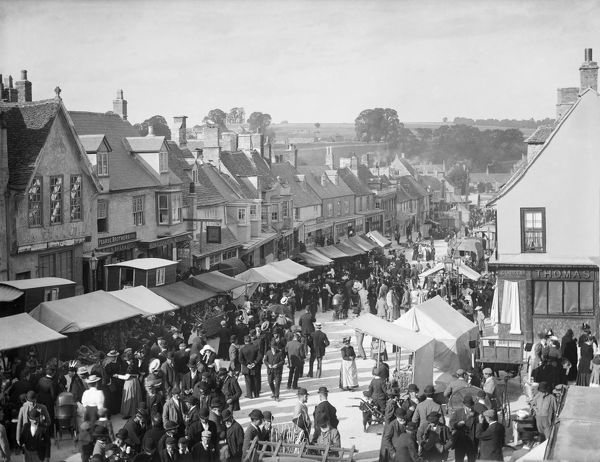 BURFORD, Oxfordshire. A view of the High Street during the Hiring Fair (Mop Fair) with stalls set out. Photographed in 1895 by Henry Taunt