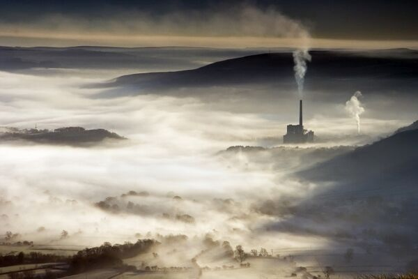 CASTLETON, Peak District, Derbyshire. Early morning view from Mam Tor looking down onto Castleton showing the valley shrouded in mist as a factory chimney adds smoke to the air