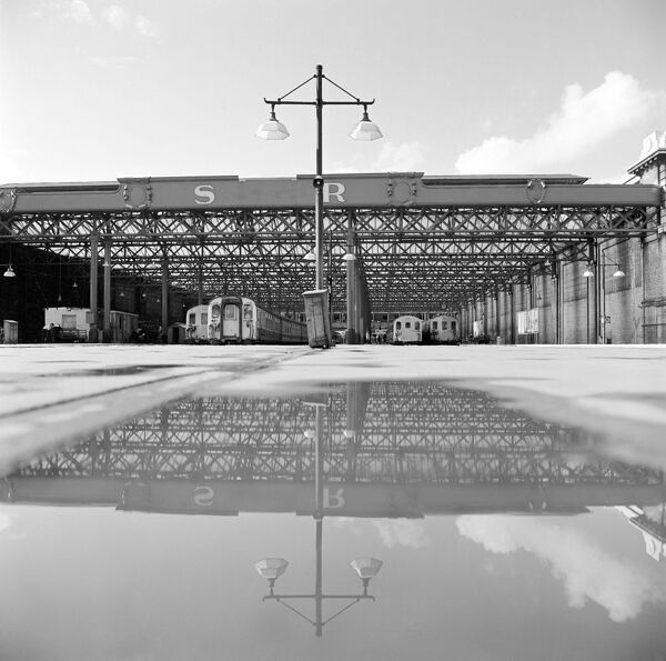 CHARING CROSS STATION, London. A view towards the train shed at Charing Cross from the exterior platforms. The train shed is partially reflected in a pool of rain water on the platform. John Gay. Date range: 1960-1972