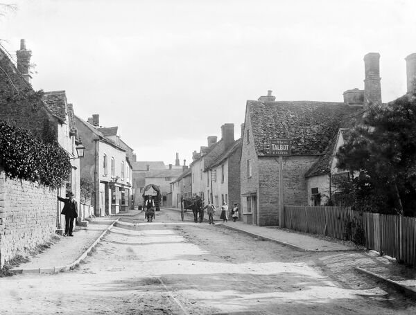 CHARLBURY, Oxfordshire. A street scene showing Thames Street with several local inhabitants, one with a wheelbarrow, standing near the Talbot public house. Photographed by Henry Taunt (active 1860 - 1922)