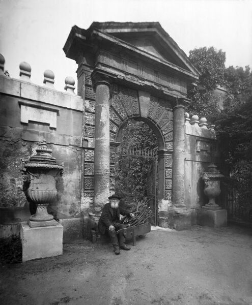 CHISWICK HOUSE, Hounslow, London. View of the Chelsea Gate, with a bearded gardener seated on his barrowload of sticks. Photographed by Newton & Co. between 1896 and 1920