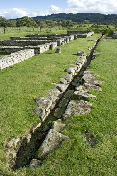 HADRIAN'S WALL: CHESTERS ROMAN FORT, Northumberland. View of the barracks showing the stone-lined drain between blocks