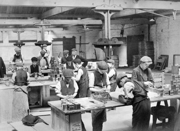 BUTLER'S WHARF, Shad Thames, London. From 1921 children had to be at least 12 years old before they could work full-time, though some of these boys look younger. They appear to be labelling tins of tea. Their work benches are made of wooden panels