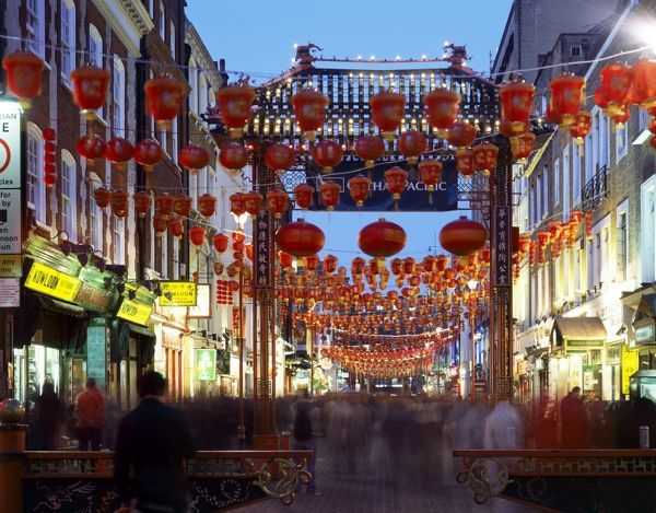 CHINATOWN, Gerrard Street, London. General view of china town at dusk showing the busy street with red chinese lanterns and entrance gateway