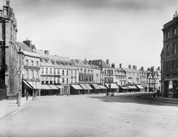 CIRENCESTER, Gloucestershire. Looking down the market place from the parish church of the capital of the Cotswolds. Showing the north side shop fronts with their awnings out over the pavement. Photographed in 1883 by Henry Taunt