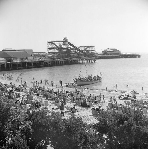 CLACTON-ON-SEA, Essex. A view of the pier complete with rollercoaster. In the foreground seaside holidaymakers lounge in deckchairs while a small boat offers sea trips. Photographed by Hallam Ashley in 1953