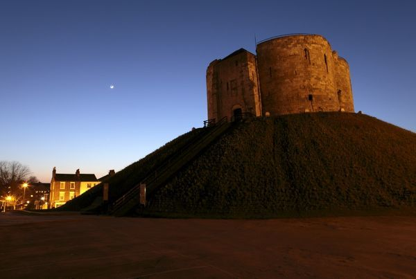 CLIFFORD'S TOWER, York, North Yorkshire. Floodlit view with moon in the sky