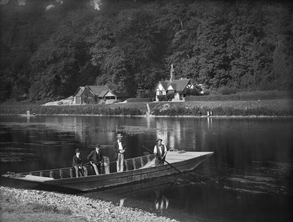CLIVEDEN FERRY, Cliveden, Taplow, Buckinghamshire. The ferryman is ready to take two men and a boy across the river. The man seated on the side of the boat holds a camera. The River Thames is wide and shallow at this point. Henry Taunt 1885