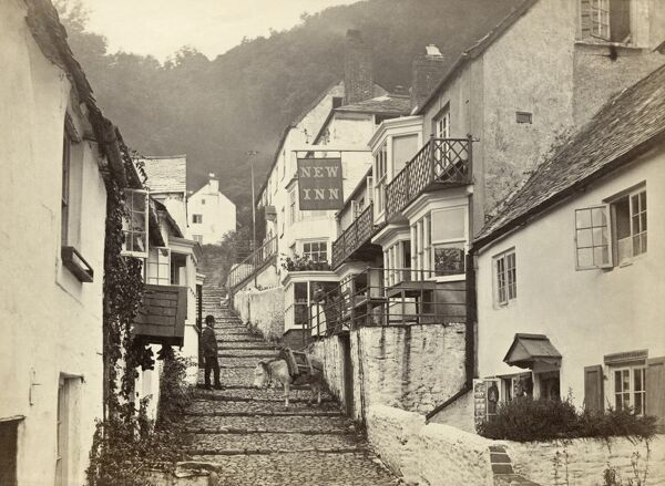 CLOVELLY, Torridge, Devon. A view up the main cobbled street in Clovelly, with a donkey on the cobbles and a woman standing on the terrace of the New Inn talking to a man below. Donkeys are still used to transport goods up the steep cobbled street in Clovelly