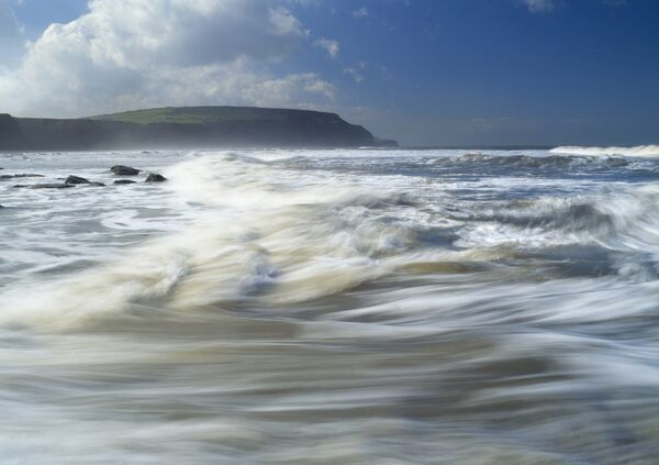 BOULBY CLIFFS, North Yorkshire. A view from Staithes across the sea towards Boulby Cliffs with the waves blurred by movement