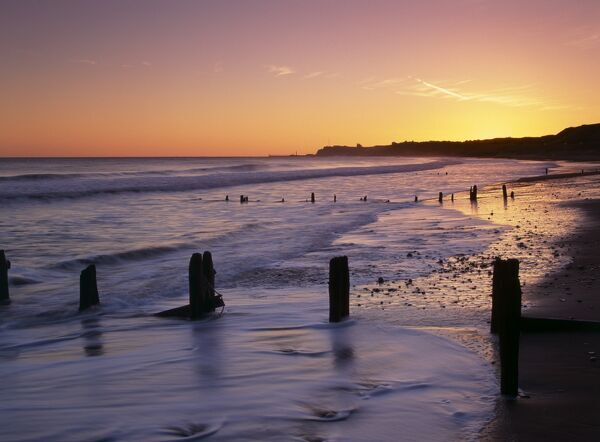SANDSEND, North Yorkshire. View at sunrise of the sandy beach & groynes looking east towards Whitby