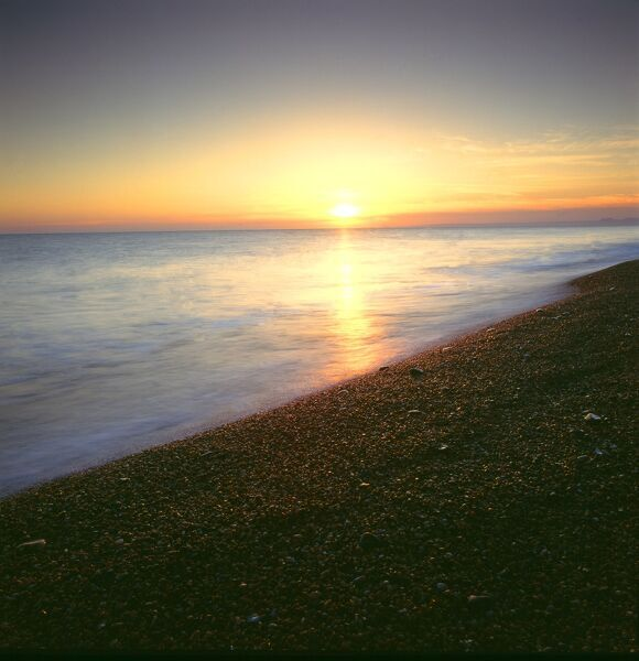 CHESIL BEACH, Dorset. A view of the beach and sea at sunset