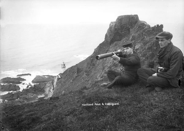 A coastguard, with telescope, keeping watch near Hartland Point lighthouse, Devon. Alfred Newton and Son 1896-1920
