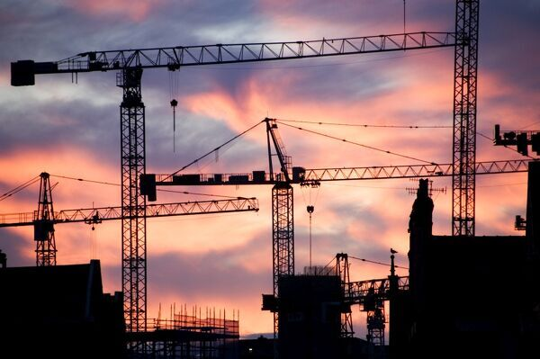 Urban landscape. A building site at sunset with cranes against a red sky