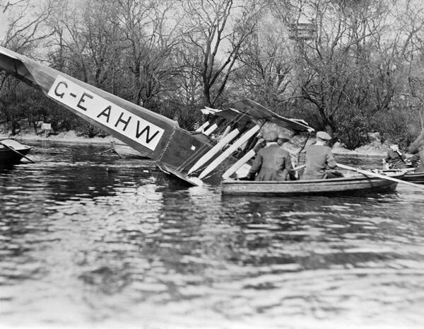 Crashed aircraft. People in rowing boat investigating the wreckage. AVRO504K in Southwark boating lake, March 1920. From a copy negative. Aerofilms Collection (see Links)